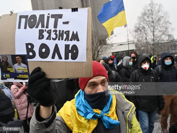 """An activist holding a placard reading """"Freedom to political prisoners"""" protests in front of Kiev's President Hotel during the Congress of Judges of..."""
