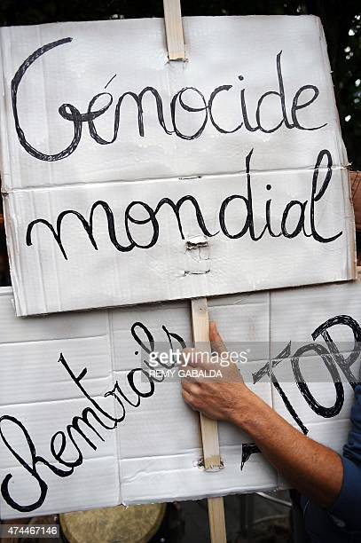 An activist holds a banner that says 'Génocide mondial chemtrails Stop' at a march against Monsanto where 'antiOGM31' cooperative and citizens are...