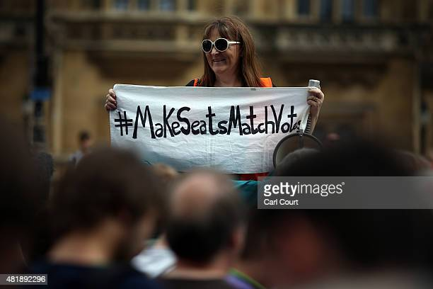 An activist holds a banner with a twitter hashtag during a Youth Parliament rally In support of voting reform on July 25 2015 in London England The...