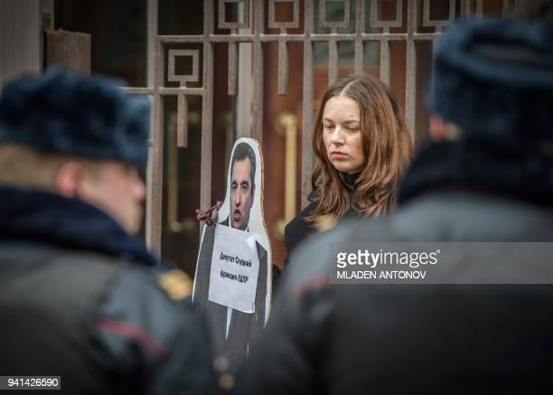 An activist holds a cardboard cut of Russian Parliament member Leonid Slutsky during a protest in front of the State Duma in Moscow on April 3 2018...