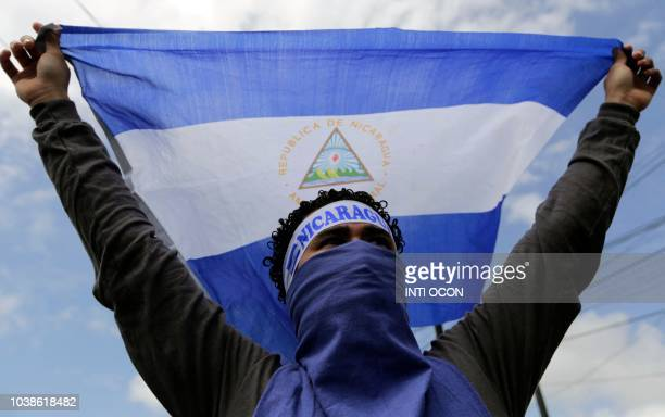 An activist holds a flag during during a protest against Nicaraguan President Daniel Ortega's government in Managua, on September 23, 2018.