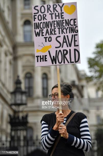 An activist holds a placard as she protests during the second day of climate change demonstrations by the Extinction Rebellion group in central...