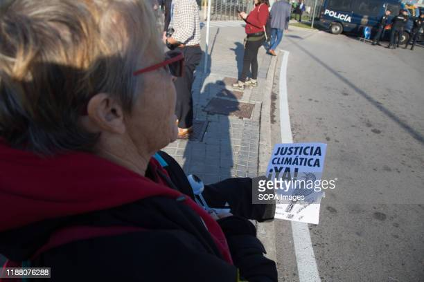 An activist holds a placard demanding climate justice during the demonstration. There was a spontaneous saucepan protest at the entrance of COP25...
