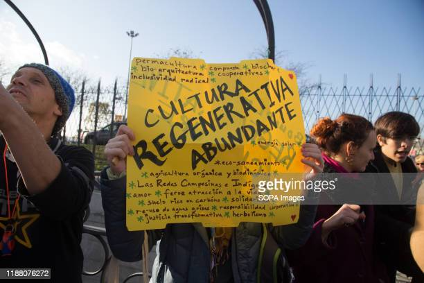 An activist holds a placard demanding sustainable economic and social There was a spontaneous saucepan protest at the entrance of COP25 where climate...
