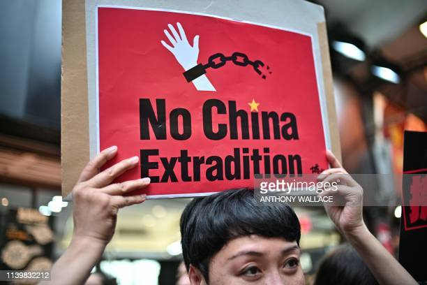 An activist holds a placard during a protest in Hong Kong on April 28 against a controversial move by the government to allow extraditions to the...