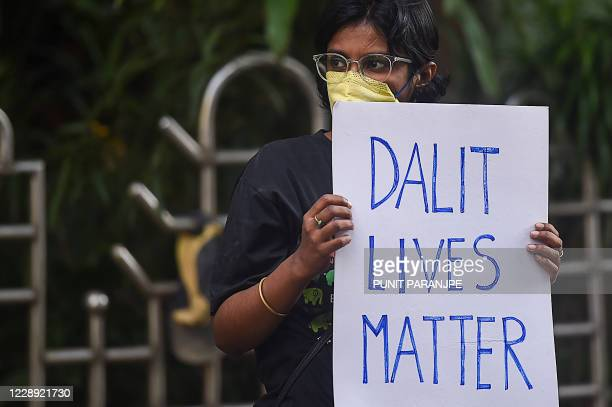 An activist holds a placard during a protest to condemn the alleged gang-rape and murder of a 19-year-old woman in Bool Garhi village of Uttar...