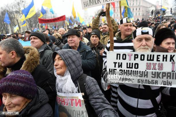An activist holds a placard reading 'Poroshenko do not destroy Ukraine' during a mass march and rally calling for the impeachment of Ukrainian...