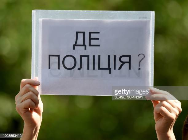 An activist holds a placard reading 'Where is the police' during a protest in front of the Ukrainian Ministry of Internal Affairs in Kiev on August 1...