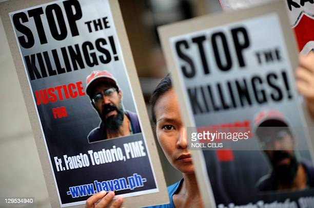 An activist holds a placard with a picture of murdered Italian priest Fausto Tentorio during a rally in front of the Department of Justice calling...
