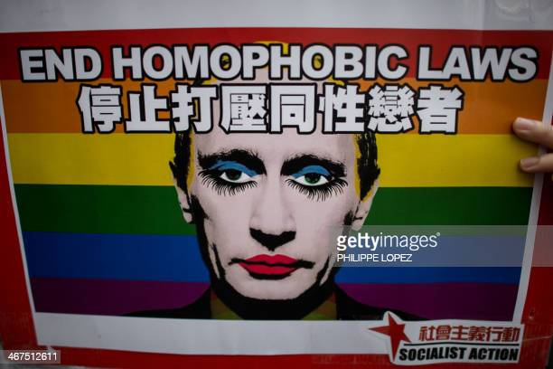 An activist holds a placard with a slogan over the face of Russian President Vladimir Putin depicted with makeup during a demonstration against...