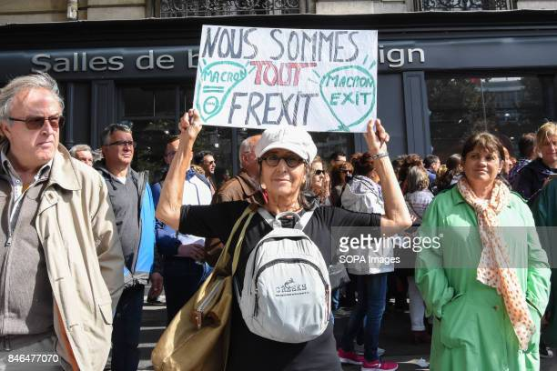 An activist holds a placard writing on it we are all Frexit 'Macron exit' take part in a protest during the nationwide strike called by various...