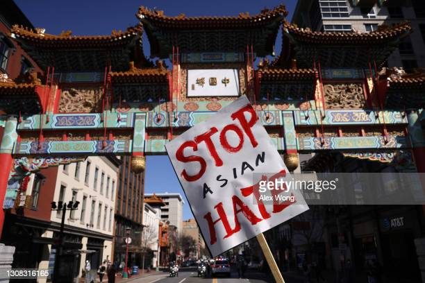 """An activist holds a sign after he marched to Chinatown from a """"DC Rally for Collective Safety - Protect Asian/AAPI Communities,"""" hosted by OCA –..."""