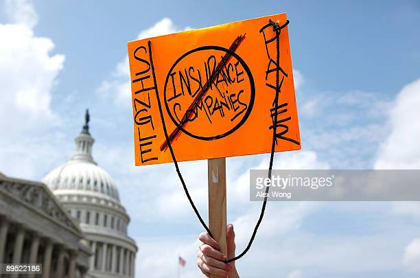An activist holds a sign as she marches on Capitol Hill after a rally on healthcare July 30 2009 in Washington DC Activists gathered to rally...