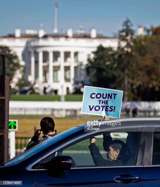 An activist holds a sign as they drive past the White House during a protest organized by Shutdown DC, on November 5, 2020 in Washington, DC. Ballot...
