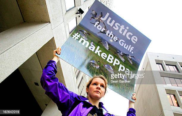 An activist holds a sign during a protest in front of the Hale Boggs Federal Building on the first day of the trial over the Deep Water Horizon oil...