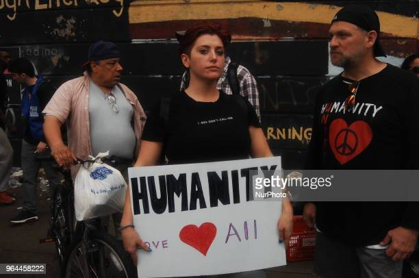 An activist holds a sign reminding people that these people are human beings and deserve to be treated as such at the Kensington Avenue and Lehigh...