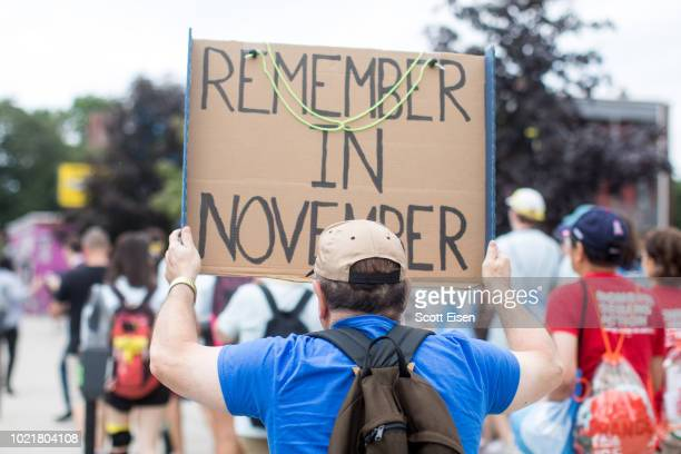 An activist holds a sign that reads Remember in November during the 50 Miles More walk against gun violence which will end with a protest at the...