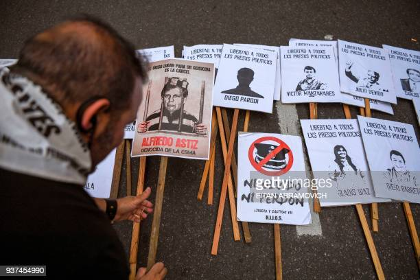 An activist holds a sign with the picture of Alfredo Astiz nicknamed 'Angel of Death' who was handed two life sentences for crimes against humanity...