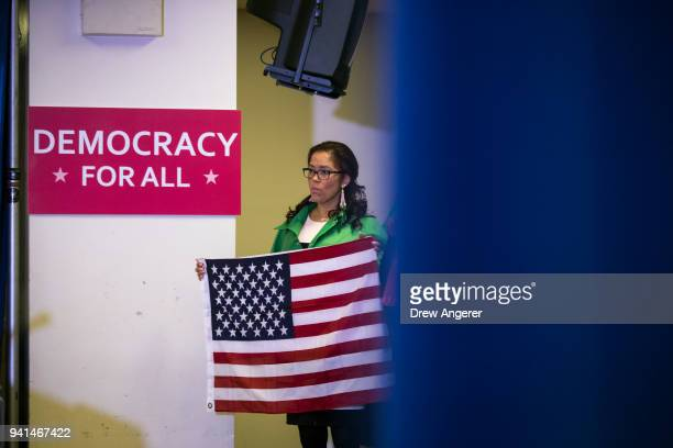 An activist holds an American flag during a press conference to announce a multistate lawsuit to block the Trump administration from adding a...