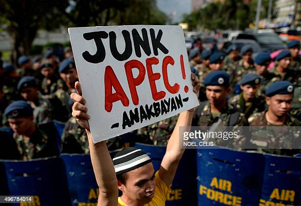 An activist holds an anti AsiaPacific Economic Cooperation banner during a protest in front of US embassy in Manila on November 12 2015 The group...