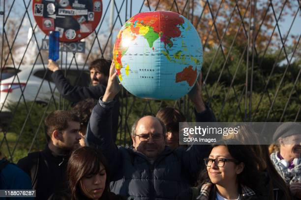 An activist holds the Earth balloon during the demonstration. There was a spontaneous saucepan protest at the entrance of COP25 where climate change...
