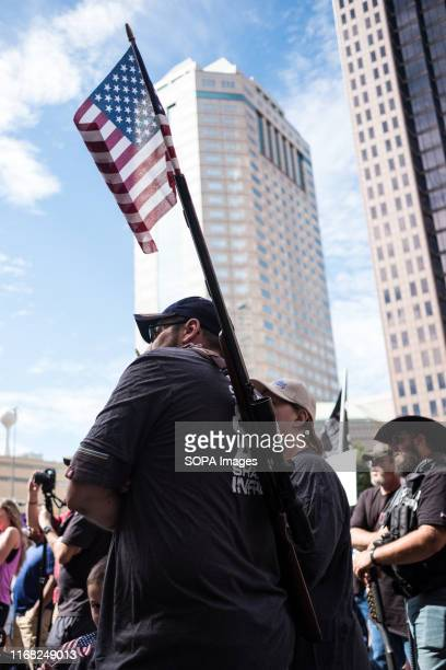 An activist holds their gun with a flag in the barrel during a progun rally against the general gun control agenda in Columbus