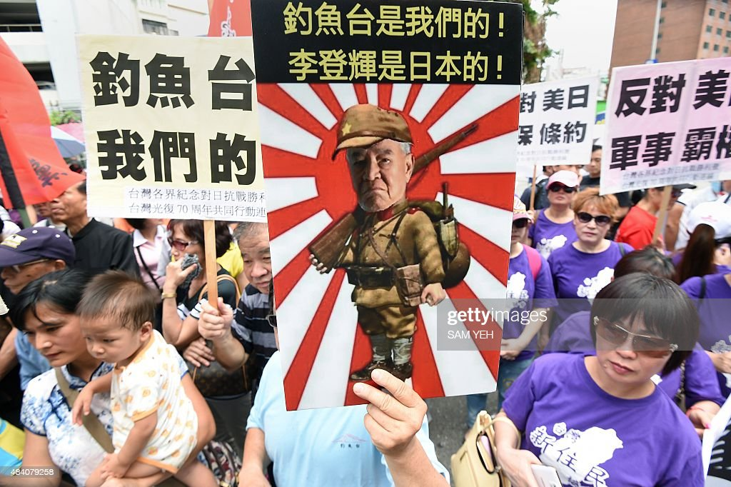 An activist holds up a placard showing former Taiwan