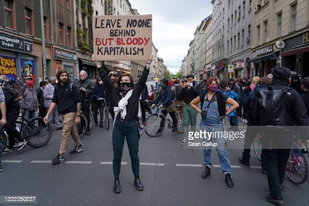 An activist holds up a sign against capitalism during scattered leftwing protests in Kreuzberg district on May Day during the novel coronavirus...