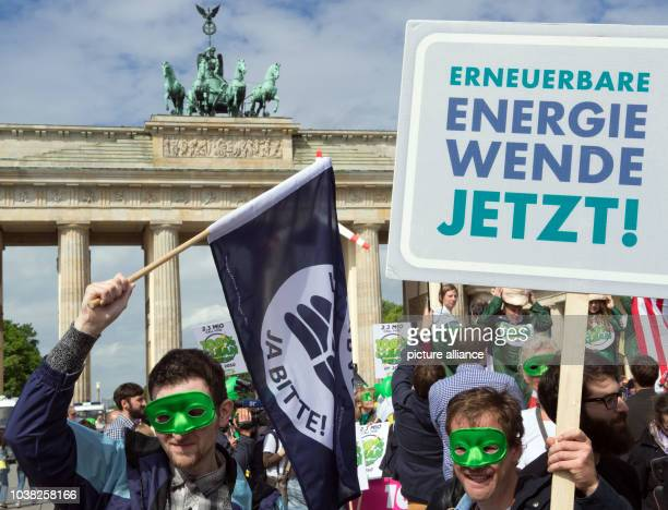 An activist holds up a sign that reads 'Erneuerbare Energie Wende Jetzt' during a rally at the Brandenburg Gate on the occasion of the 6th...