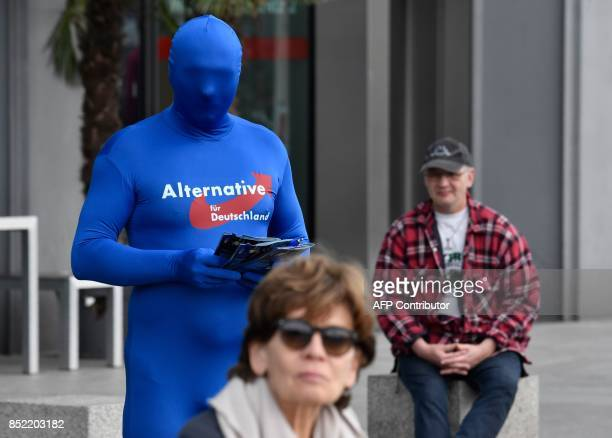 An activist in a suit distributes campaign flyers for the farright Alernative for Germany party during a local campaigning event in Berlin on...