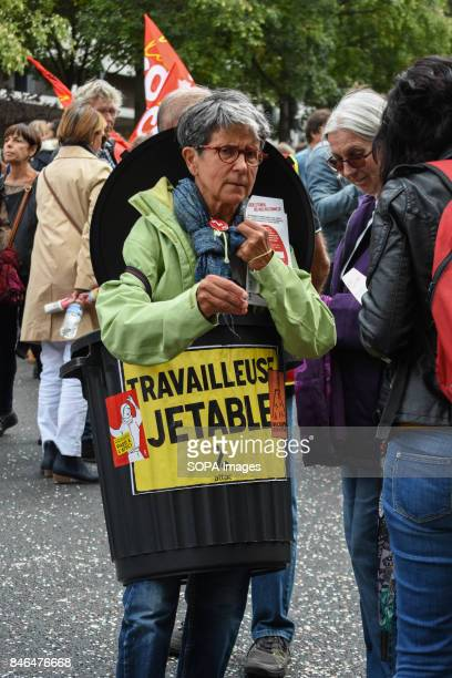 An activist inside a plastic bin writing on it throwaway workers' take part in a protest during the nationwide strike called by various French unions...