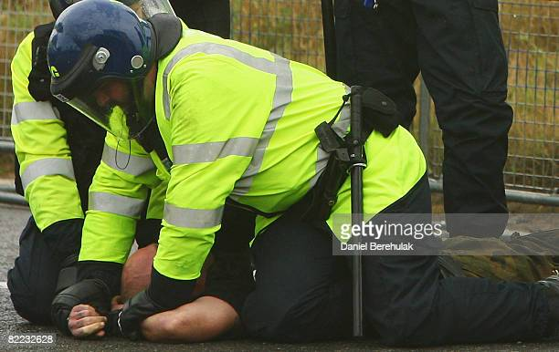 An activist is forcefully arrested by riot police after being removed from the gates of Kingsnorth power station on August 9 2008 in Kingsnorth...