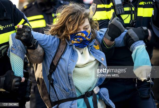 An activist is removed by police as during a demonstration by Extinction Rebellion outside the Overtoom in Amsterdam-West, as police move some of the...