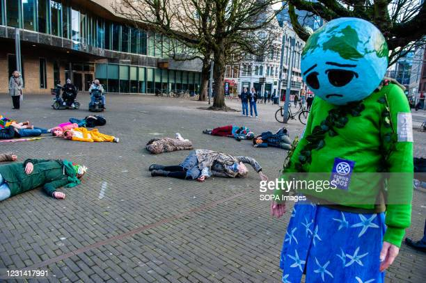 An activist is seen wearing an Earth head with a sad smile during a Die In action. As a part of the Spring Rebellion campaign of Extinction...