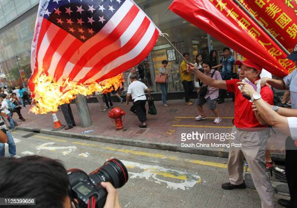 An activist is suppressed by police as he waves a burning JapanUS combined flag during a demonstration from Victoria Park to the Japanese Consulate...