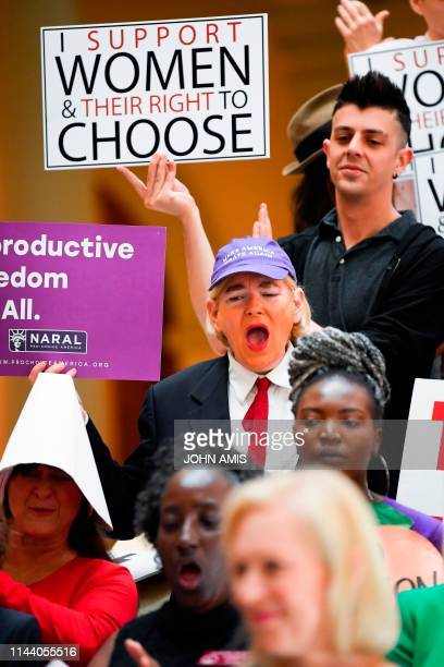 An activist made up in the likeness of the US president listens as Democratic presidential candidate Sen Kirsten Gillibrand addresses an event at the...