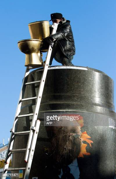 An activist of an Ukrainian students organization installs a golden toilet on a pedestal where a statue of Lenin used to stand before it was ripped...