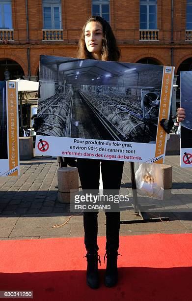 An activist of animal rights association L214 hold a banners reading ' To produce Foie Gras around 90% of ducks are confined in battery cages''...