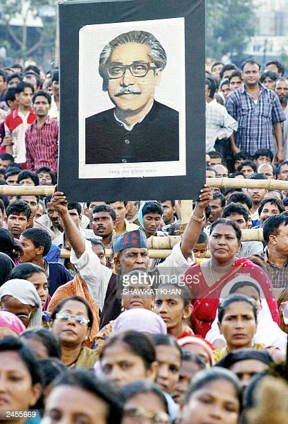 An activist of Bangladesh's main opposition party the Awami League holds a portrait of country's founder Sheikh Mujibur Rahman above the heads of...