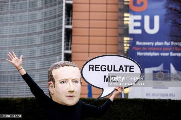 "An activist of environmental NGO Avaaz wearing a mask depicting Facebook CEO Mark Zuckerberg holds a banner reading ""Regulate me"" during an action..."