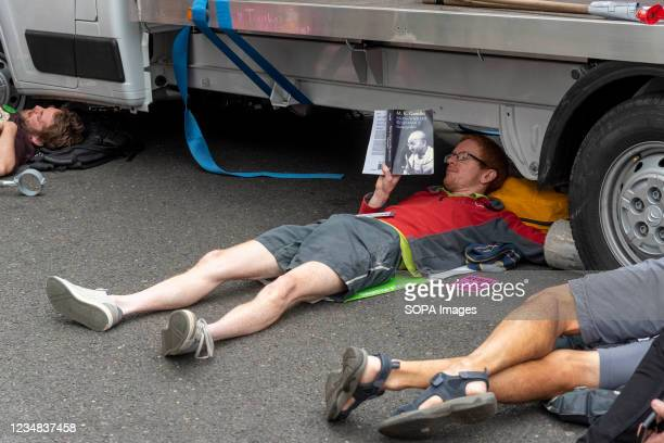 An activist of Extinction Rebellion reads M. K. Gandhis Non-Violent Resistance book while being locked to a van blocking the road during the...