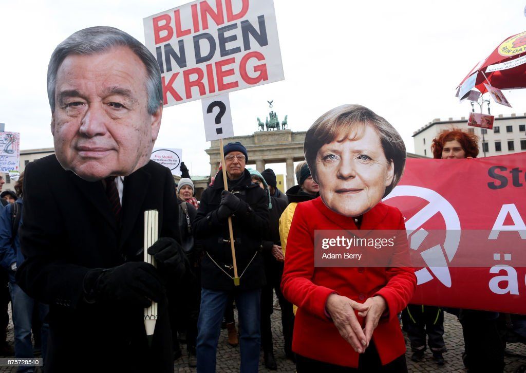 An activist of German Chancellor Angela Merkel (CDU, R) and one wearing one of United Nations Secretary General Antonio Guterres pose with a giant pencil as though they are about so sign a treaty banning nuclear weapons during a demonstration against the devices on November 18, 2017 in Berlin, Germany. About 700 demonstrators protested against the current escalation of threat of nuclear attack between the United States of America and North Korea. The event was organized by peace advocacy organizations including the International Campaign to Abolish Nuclear Weapons (ICAN), which won the Nobel Prize for Peace this year.