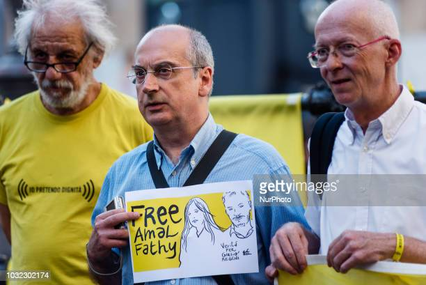 An activist of human rights organization Amnesty International holds a placard with a sketch of Amal Fathy and Giulio Regeni and saying quotFree Amal...