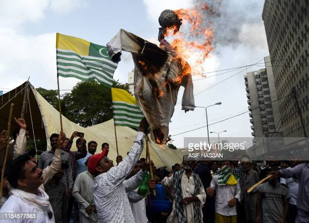An activist of Pakistan Peoples Party holds a burning effigy of Indian Prime Minister Narendra Modi during a rally for the death anniversary of slain...