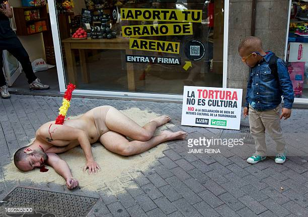 An activist of the AnimaNaturalis organization protests halfnaked covered with fake blood against bullfighting in Palma de Mallorca on May 22 2013...