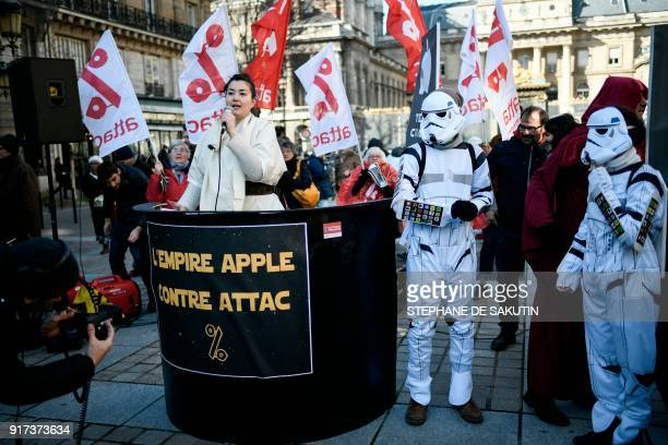 An activist of the Association for the Taxation of Financial Transactions and Citizen's Action speaks behind a placard reading The Apple empire...