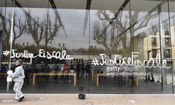 An activist of the Association for the Taxation of financial Transactions and Citizen's Action walks after painting on the Apple Store window during...