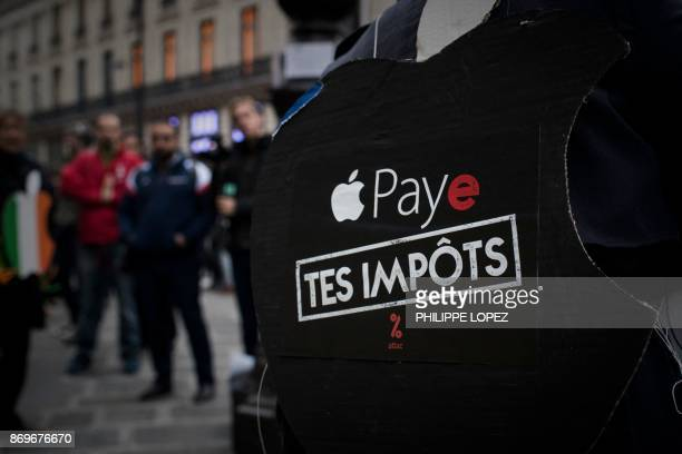 An activist of the 'Attac' network bears a sign reading 'pay your taxes' during a protest against tax evasion outside an Apple shop on the release...