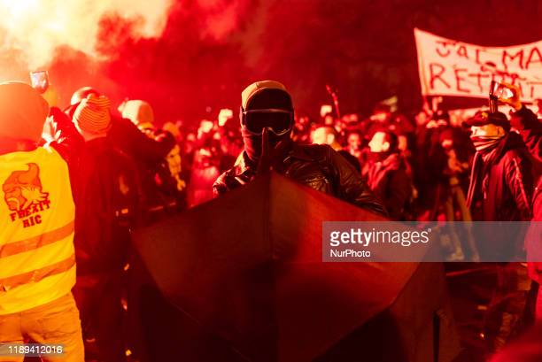 An activist of the Black Bloc with a fully masked face and equipped with an umbrella signs the victory sign with his fingers in the middle of a cloud...