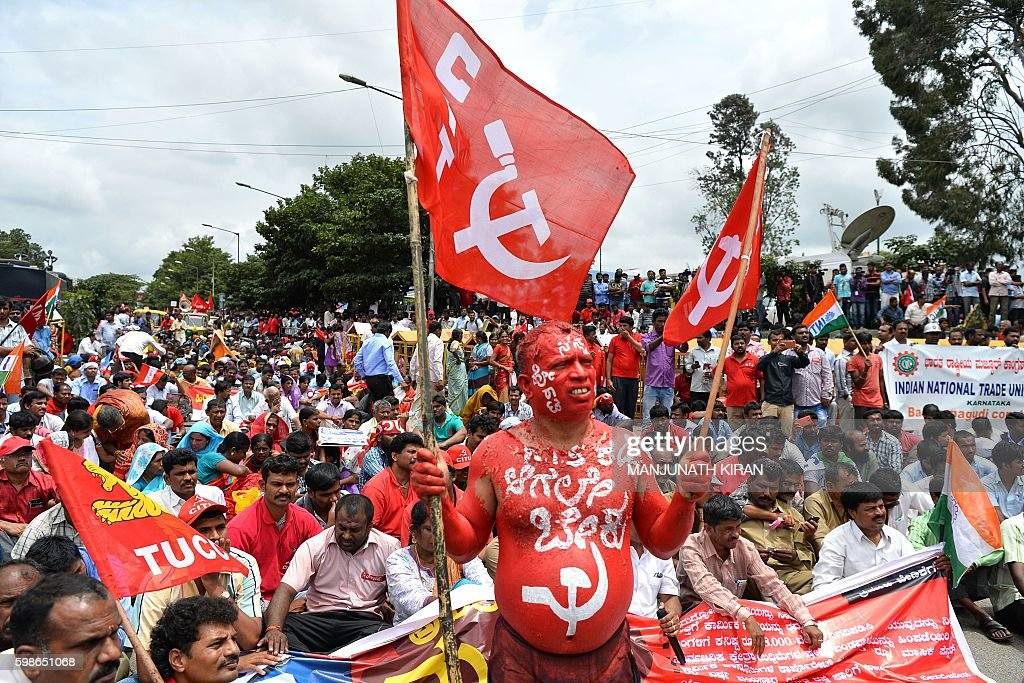An activist of the Centre of Indian Trade Union (CITU) with his body painted holds a CITU flag during a protest in Bangalore on September 2, 2016, during an all India strike staged by various trade unions. A countrywide general strike has been called by various trade unions against alleged the anti-worker and anti-people policies of the Indian government in response to its meagre raise in minimum wage to Rs. 9100 (USD 136) per month. / AFP / MANJUNATH